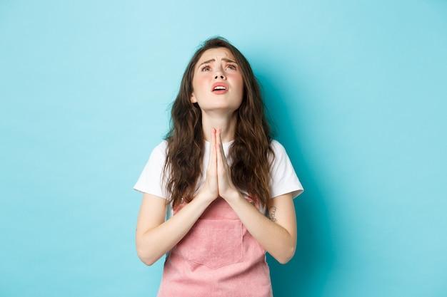 Mujer morena joven desesperada rogando a dios, tomados de la mano en oración y mirando al cielo con rostro esperanzado, suplicando por el sueño hecho realidad, de pie contra el fondo azul.