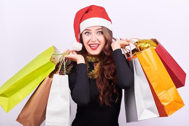 Mujer morena joven elegante con los bolsos de compras coloridos