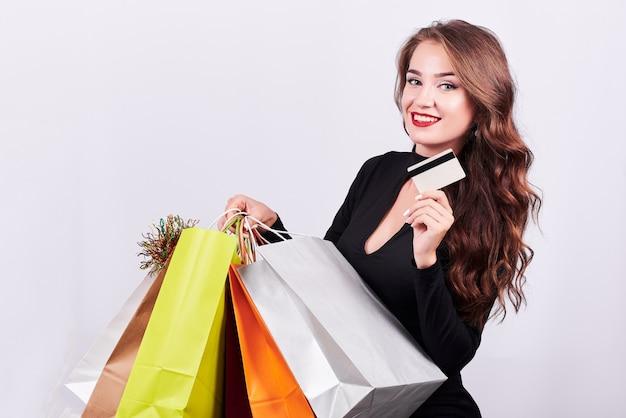 Mujer morena joven elegante que sostiene bolsos de compras coloridos