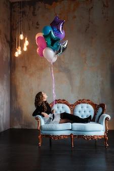 Mujer morena joven encantadora que sostiene un paquete grande de globos del helio que mienten en el sofá