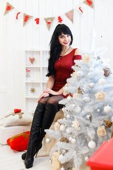 La mujer morena joven feliz en el vestido rojo que se sentaba dentro en una navidad adornó el interior.