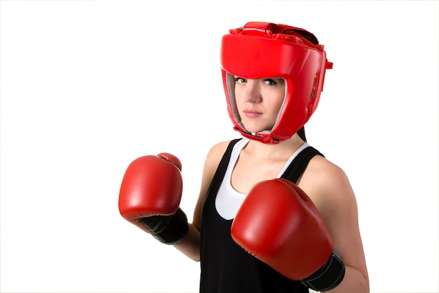 Mujer morena joven en guantes de boxeo rojos y casco haciendo impacto.