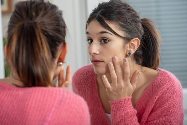 Mujer morena joven hermosa que se mira en el espejo