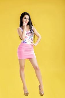 Mujer morena joven pensativa en falda rosa y camiseta sin mangas en amarillo
