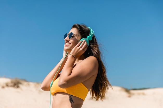 Mujer morena joven que escucha la música en auriculares