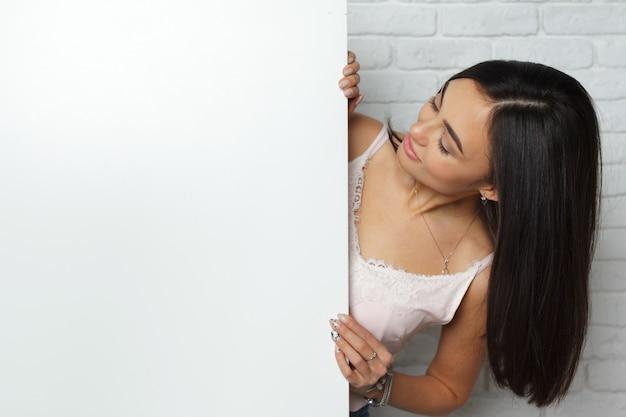 Mujer morena joven que lleva a cabo al tablero blanco en blanco grande con el espacio de la copia