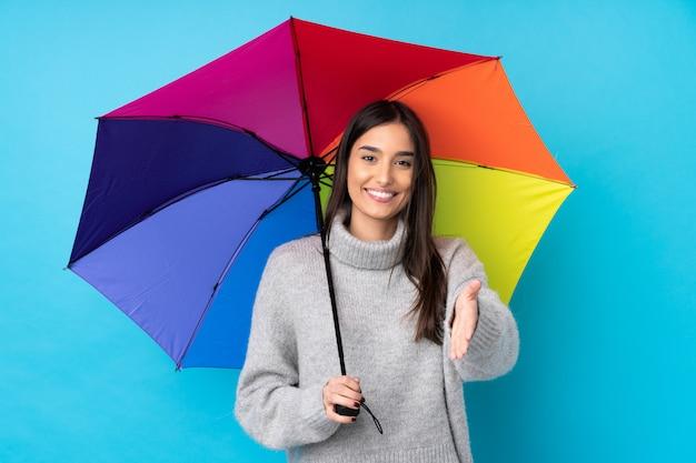 Mujer morena joven que sostiene un paraguas sobre el apretón de manos aislado de la pared azul después del buen trato