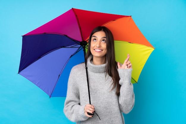 Mujer morena joven que sostiene un paraguas sobre la pared azul aislada con cruzar los dedos