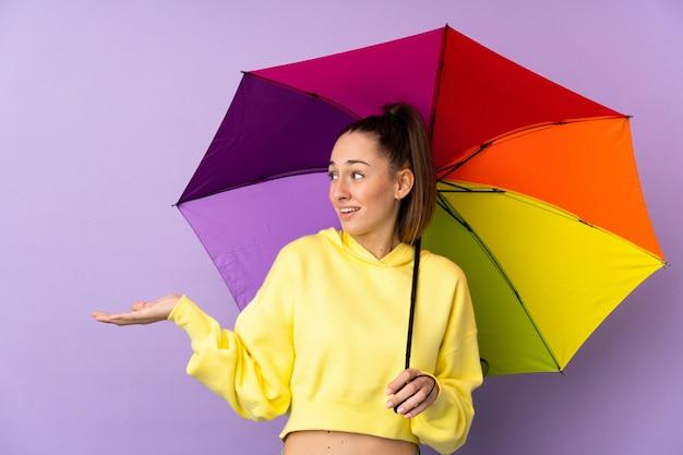 Mujer morena joven que sostiene un paraguas sobre la pared púrpura aislada con expresión facial sorpresa