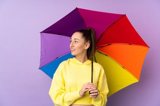 Mujer morena joven que sostiene un paraguas sobre la pared púrpura aislada con expresión feliz
