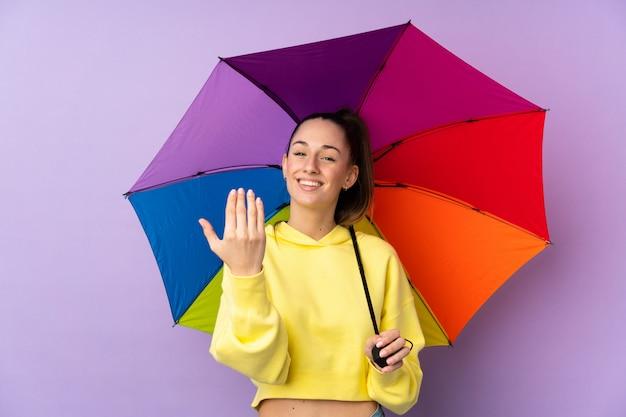 Mujer morena joven que sostiene un paraguas sobre la pared púrpura aislada que invita a venir con la mano. feliz de que hayas venido
