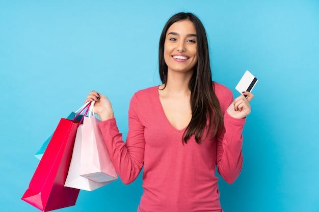Mujer morena joven sobre la pared azul aislada que sostiene bolsos de compras y una tarjeta de crédito
