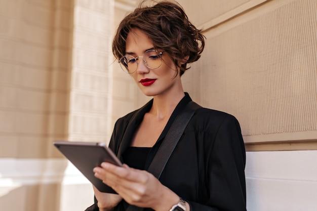 Mujer morena con labios rojos posando sosteniendo la tableta afuera. mujer elegante con pelo corto en traje negro y anteojos posando al aire libre.
