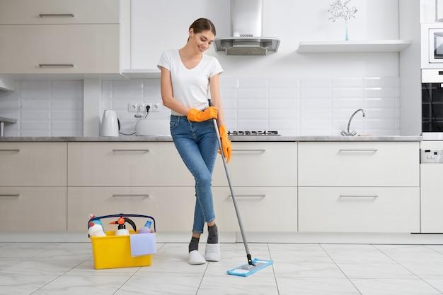 Mujer morena lavando el piso en la cocina