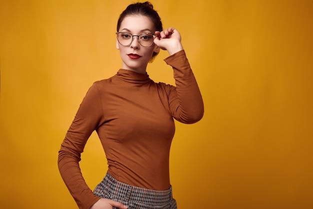 Mujer morena de moda vistiendo cuello alto y gafas sobre fondo amarillo