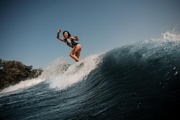 Mujer morena navegando en una tabla de surf en el mar