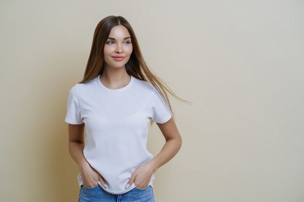 La mujer morena pensativa mira a un lado, usa una camiseta blanca informal, mantiene las manos en los bolsillos y mira