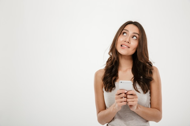 Mujer morena pensativa que sostiene el teléfono inteligente y mirando hacia arriba sobre gris