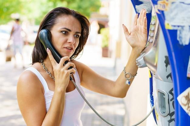 Mujer morena positiva que sostiene las llamadas del receptor de teléfono a través del teléfono de papelería en la calle turística.