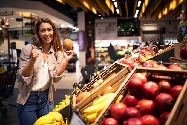 Mujer morena positiva sosteniendo coco en el departamento de frutas de la tienda de comestibles