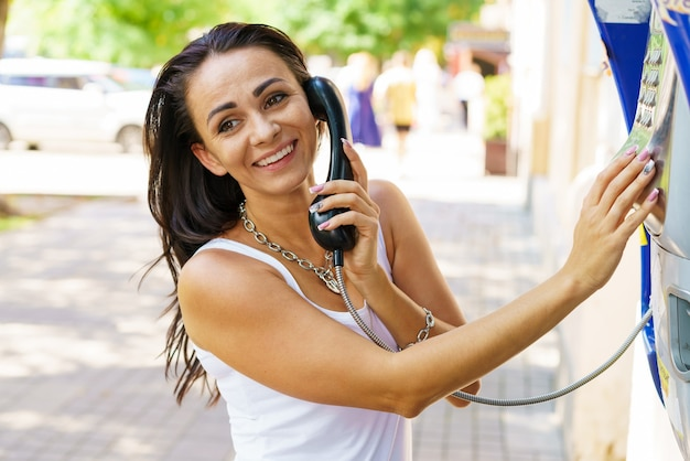 Mujer morena positiva sosteniendo llamadas telefónicas a través del teléfono de papelería en la calle, turista hablando por teléfono público trabajando con monedas, feliz con la comunicación internacional en un día soleado de verano