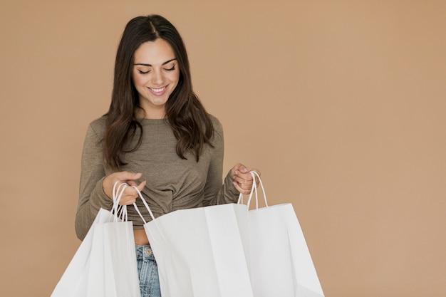 Mujer morena que mira en bolsos de compras