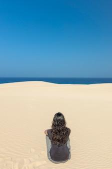 Mujer morena que mira el mar en fuerteventura, españa.
