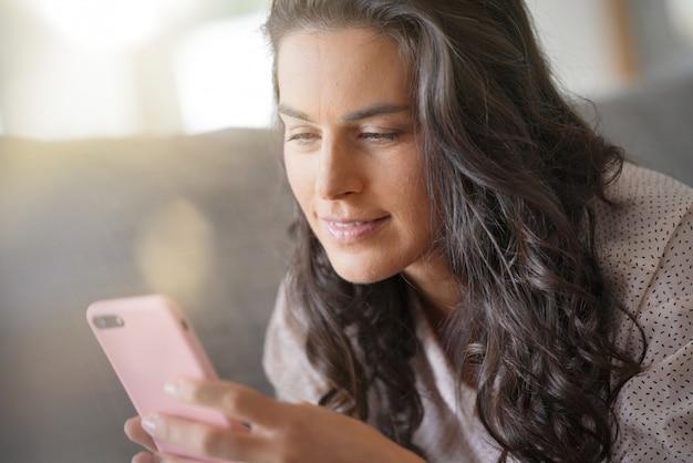 Mujer morena que se relaja en el sofá, conectado con el teléfono inteligente
