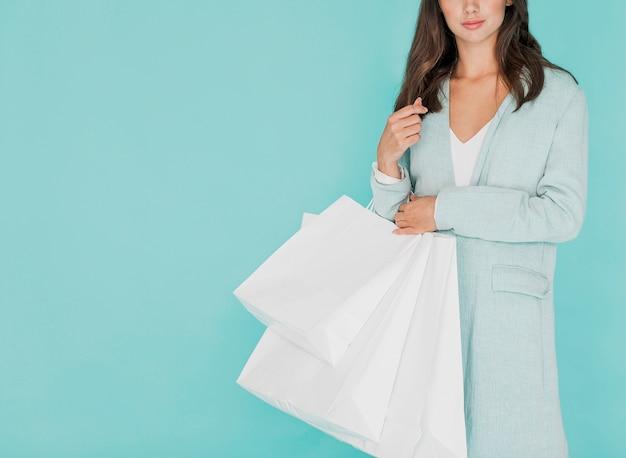 Mujer morena que sostiene bolsos de compras blancos