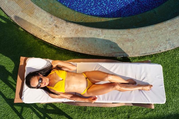 Mujer morena relajante en una hamaca en un club de playa