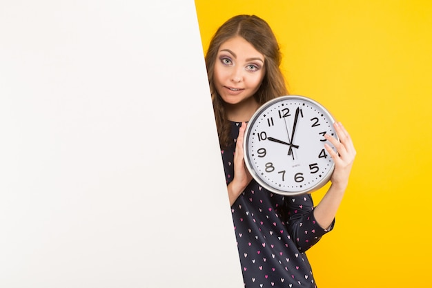 Mujer morena con relojes y pancarta en blanco