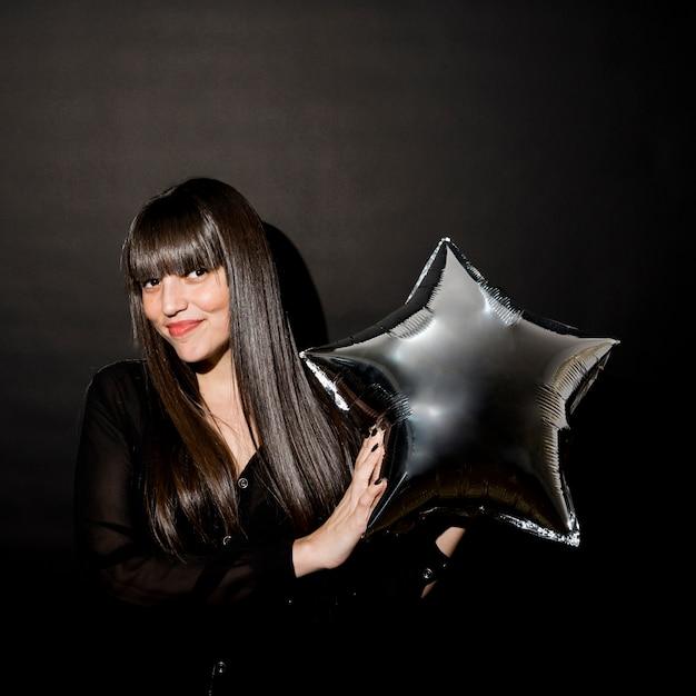 Mujer morena riendo en ropa de noche con globo