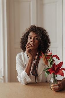 Mujer morena rizada de ojos marrones en blusa blanca y pañuelo de seda toca la cara, mira al frente y sostiene un jarrón con flores rojas