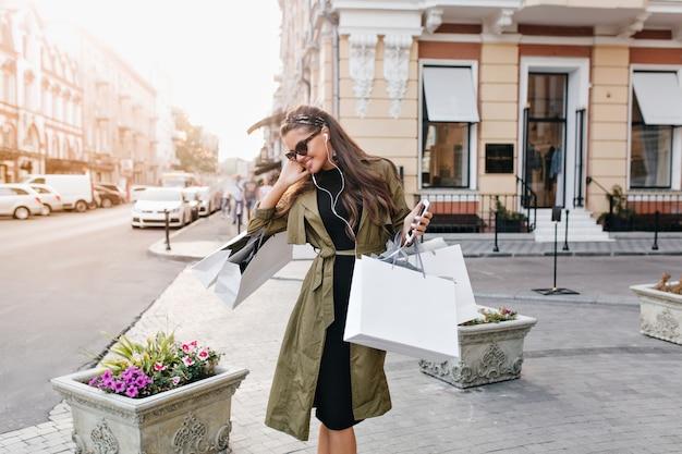 Mujer morena romántica en traje de otoño elegante mirando hacia abajo, sosteniendo las compras