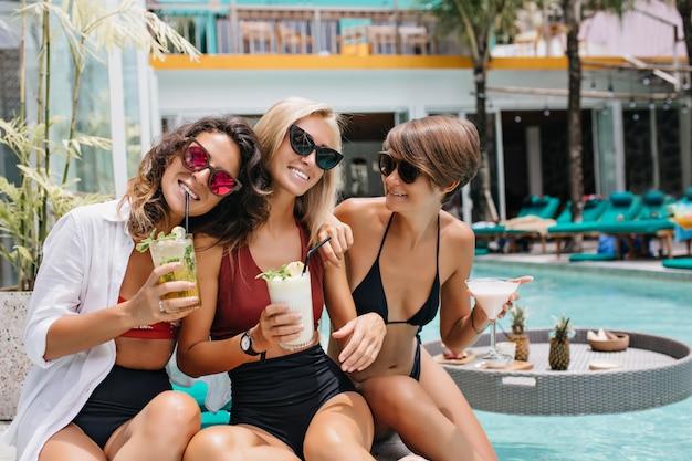 Mujer morena romántica en vasos de color rosa bebiendo cócteles durante la sesión de fotos con amigos. señoras fascinantes pasando el fin de semana en la piscina.