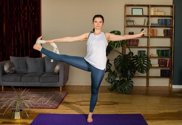 Mujer morena en ropa deportiva realiza una pose de yoga con un cinturón sobre una estera en la habitación