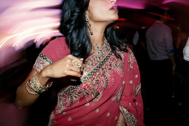 Mujer morena en sari rosa se encuentra en la multitud de personas
