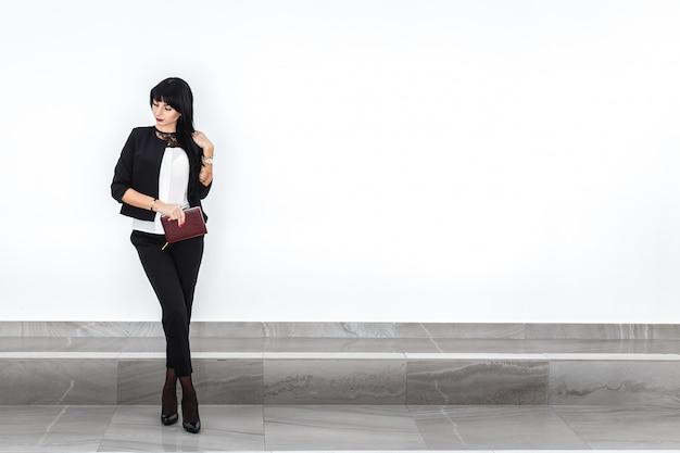 La mujer morena seria atractiva joven con un cuaderno se vistió en un traje de negocios negro que se oponía a la pared blanca en una oficina.