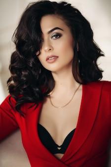 Mujer morena sexy en chaqueta roja seductora.
