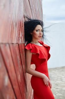 Mujer morena sexy en un vestido rojo está de pie cerca de la puerta roja.