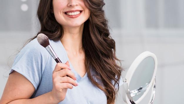 Mujer morena sonriente con el cepillo y el espejo cosmético
