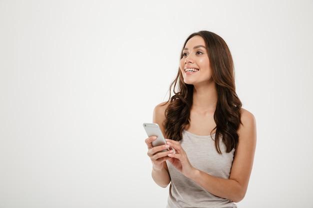 Mujer morena sonriente que sostiene smartphone y que mira lejos sobre gris