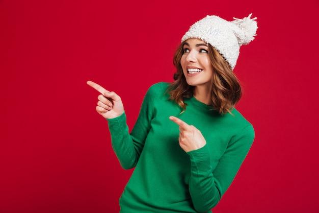 Mujer morena sonriente en suéter y sombrero gracioso apuntando lejos