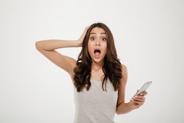 Mujer morena sorprendida con teléfono inteligente sosteniendo la cabeza y mirando a la cámara sobre gris