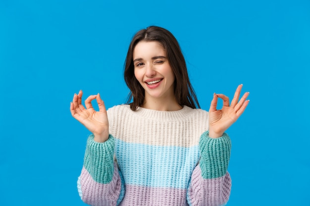 Mujer morena con suéter de invierno haciendo señal ok