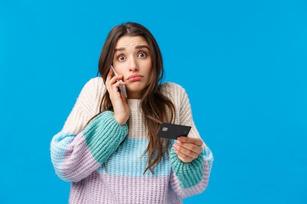 Mujer morena con suéter de invierno con tarjeta de crédito y llamando a alguien