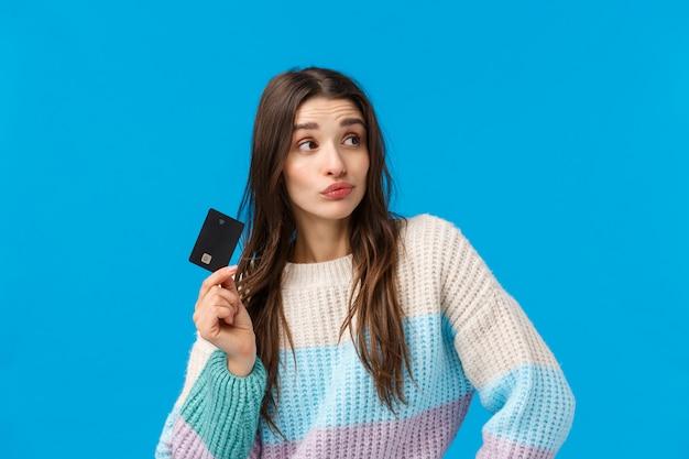 Mujer morena con suéter de invierno con tarjeta de crédito
