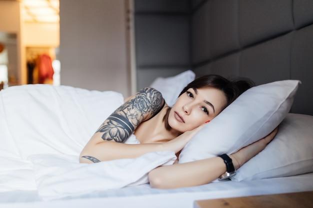 Mujer morena con tatuaje yace en la cama sobre la almohada en la mañana en el moderno apartamento de moda