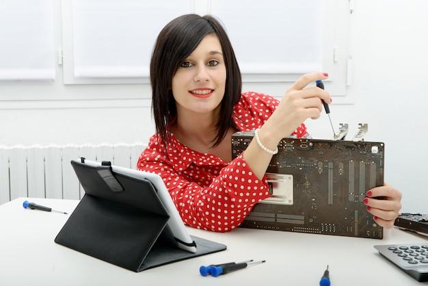 Mujer morena técnico repara una computadora
