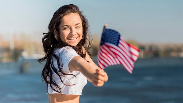 Mujer morena de tiro medio sosteniendo 2 banderas de estados unidos cerca del lago